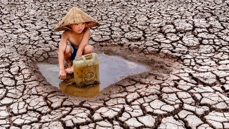 Un copil adună pentru familia lui ultimele picături de apă, de pe un câmp ars de soare